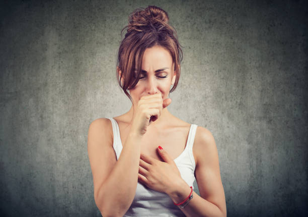 Sick woman coughing with pain Young woman having asthma problems and coughing badly covering mouth and holding hand on chest. heartburn throat pain stock pictures, royalty-free photos & images