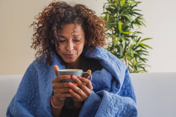 kranke frau trinkt heißgetränk bei kaltem wetter - erkältung und grippe stock-fotos und bilder
