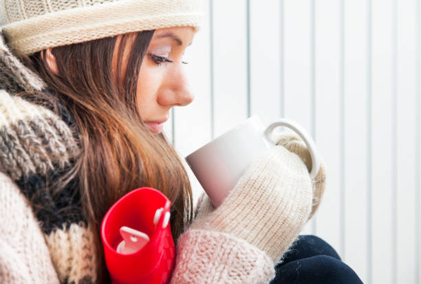 Sick woman freezing and drinking tea Sick young woman freezing at home by the radiator hot water bottle stock pictures, royalty-free photos & images