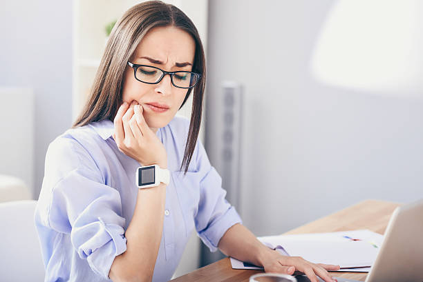 Sick woman having a tooth ache. Can nor resist it. Serious young woman using laptop and suffering from toothache. toothache stock pictures, royalty-free photos & images