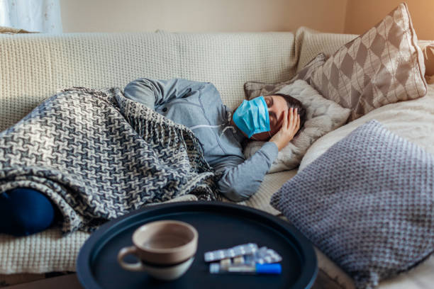 Sick woman having flu or cold. Girl lying in bed wearing protective mask by pills and water on table