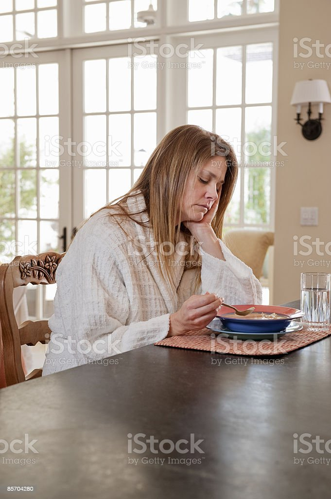 Sick Woman Having Soup at Kitchen Counter royalty-free stock photo