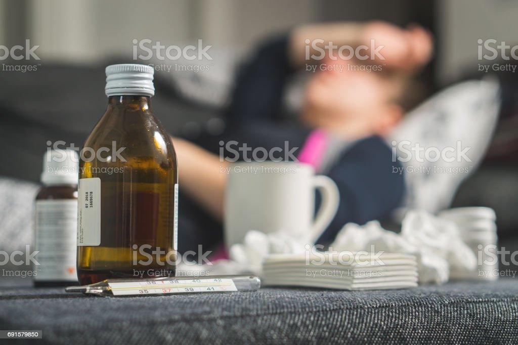 Mujer enferma sostiene la cabeza y la frente con mano y brazo. Medicina, termómetro, bebida caliente y toallas de papel sucio en frente. Persona que tiene gripe, fiebre y dolor de cabeza en el sofá del sofá. Cogió frío en invierno. - foto de stock