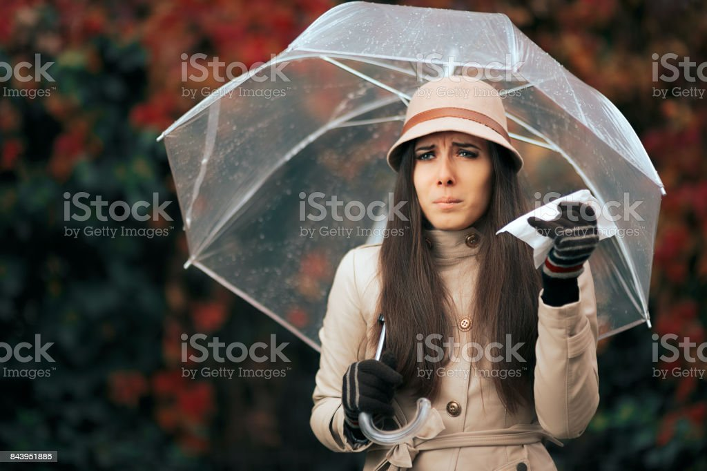 Sick Woman Holding  Umbrella in Autumn Rain Suffering from Allergies stock photo