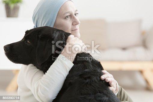 istock Sick woman hugging dog 855393714