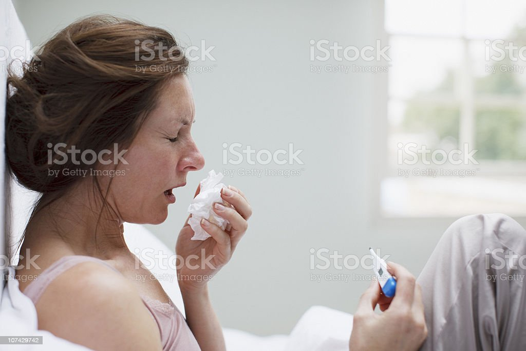 Sick woman in bed blowing nose royalty-free stock photo