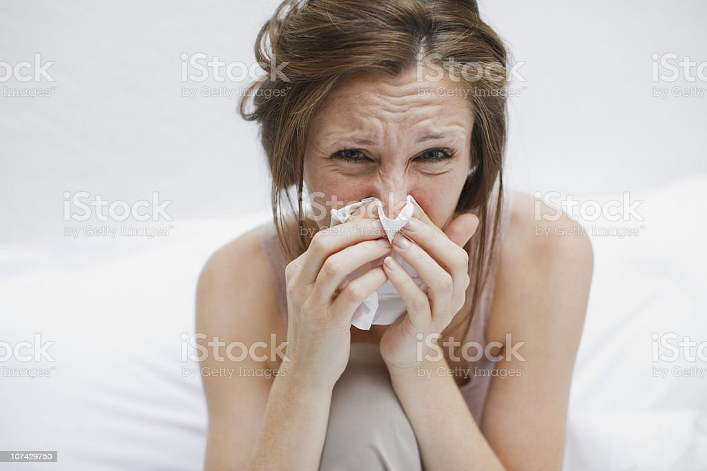 Sick woman in bed blowing nose stock photo