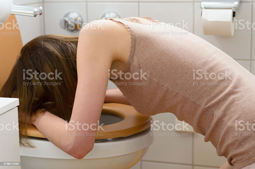 Sick woman in front of toilet stock photo
