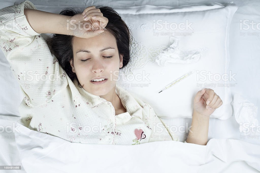 Sick woman in pajamas resting on an all-white bed royalty-free stock photo