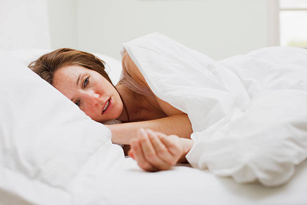Sick woman laying in bed under blanket stock photo