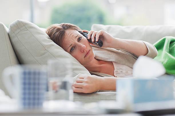 Sick woman laying on sofa talking on telephone stock photo
