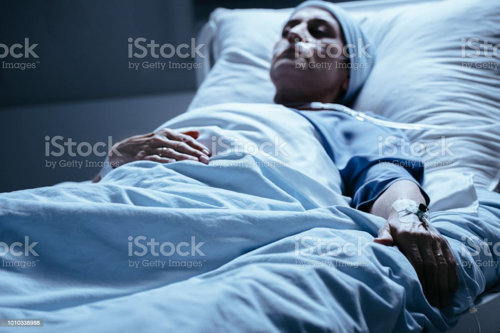Sick Woman Lying In Hospital Bed With Venflon On Hand