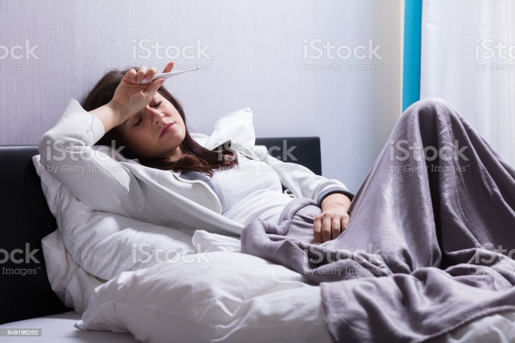 Sick Woman Lying On Bed Holding Thermometer stock photo