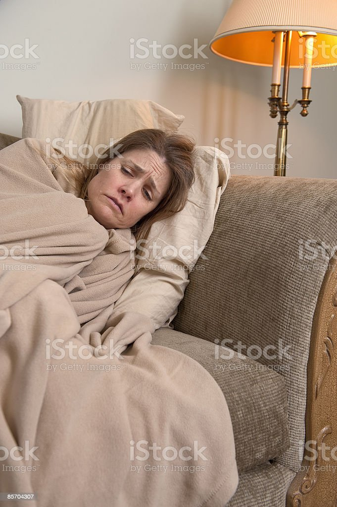 Sick Woman Lying on Couch Huddled in Blanket royalty-free stock photo