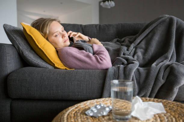 Kranke Frau liegt auf Sofa und ruft Arzt auf Handy – Foto