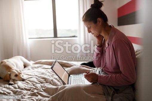 Sick woman making an appointment with doctor via internet with her dog on bed
