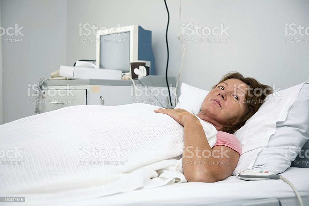 Mature woman lying on bed in hospital ward