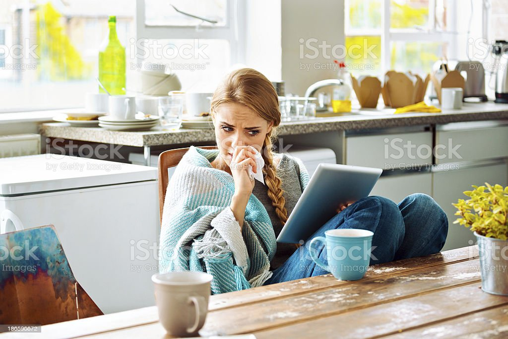 Sick woman Young woman has a cold, sitting in a kitchen wrapped in blanket and using a digital tablet. 20-24 Years Stock Photo