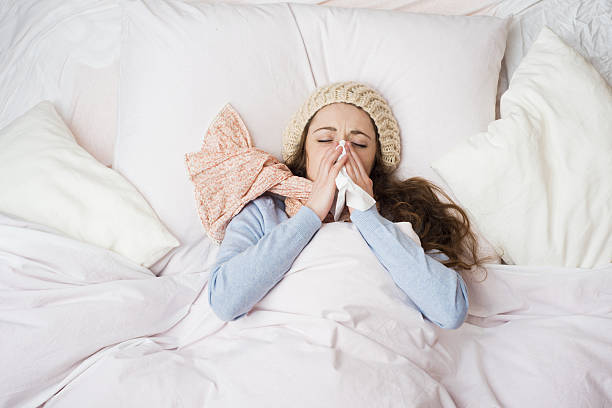 Sick woman Sick woman with thermometer is lying in bed. She has cold, flu and high fever. cold virus stock pictures, royalty-free photos & images