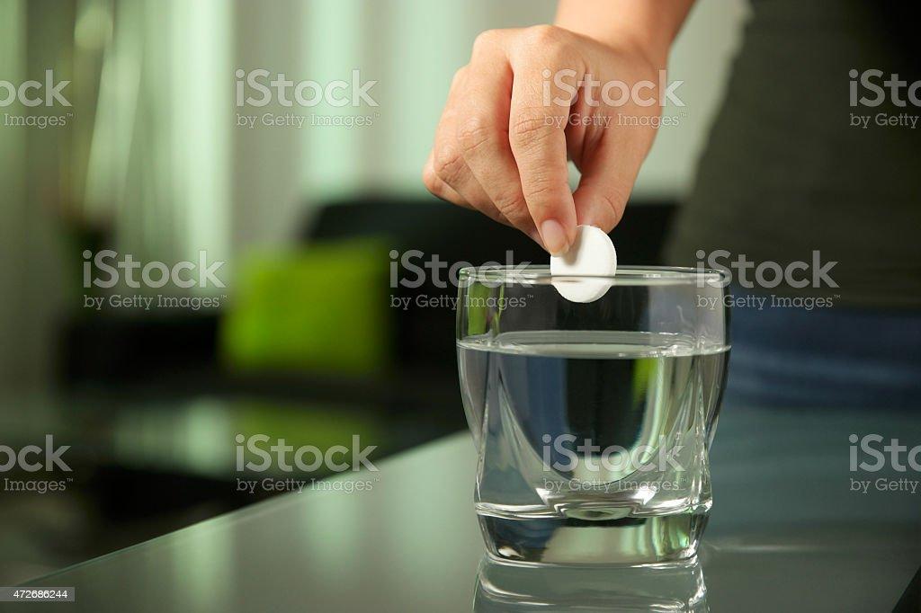 Kranke Frau steht spritzigen Tablet Aspirin In Glas Wasser – Foto