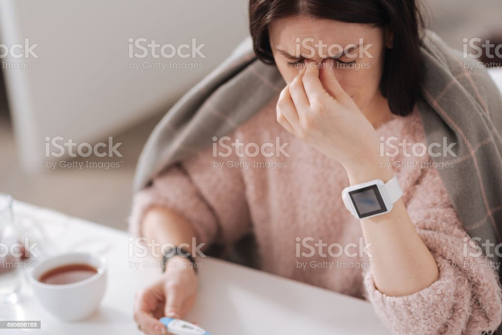 Sick woman putting fingers on her nose foto de stock royalty-free