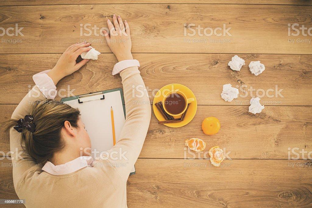 Sick woman sleeping on office desk stock photo