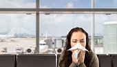 istock sick woman sneezing at the  airport 486655506
