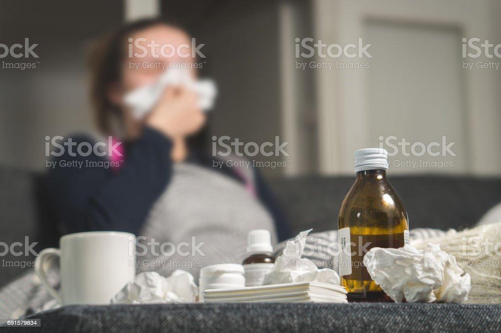 Mujer enferma estornudos al tejido. Medicina, bebida caliente y toallas de papel sucio en frente. Chica cogió frío. Jarabe para la tos y pañuelos en la tabla. Muy enfermo sentirse mal y tener fiebre. - foto de stock