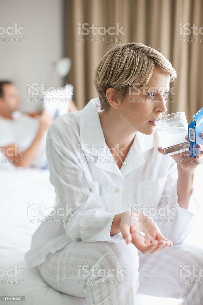Sick woman taking antacid stock photo