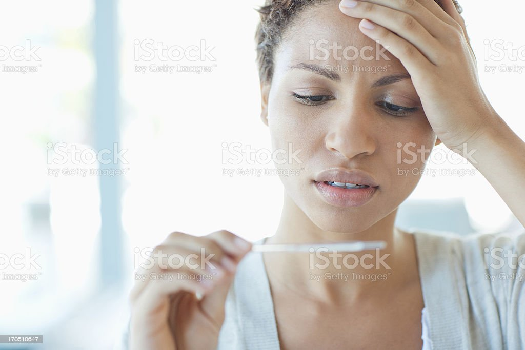 Sick woman taking her temperature stock photo