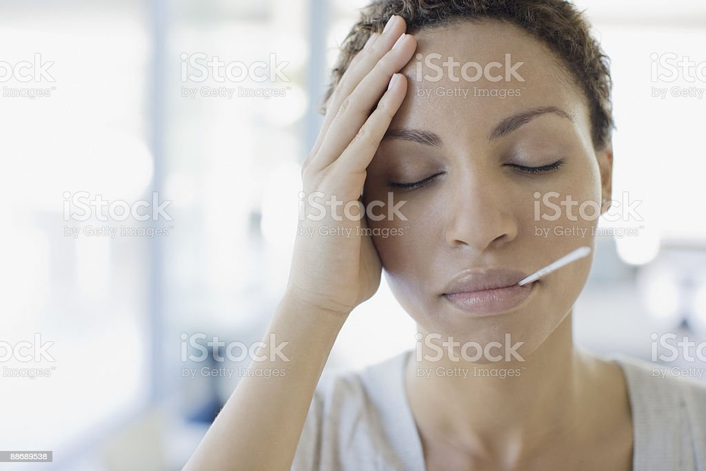 Sick woman taking her temperature royalty-free stock photo