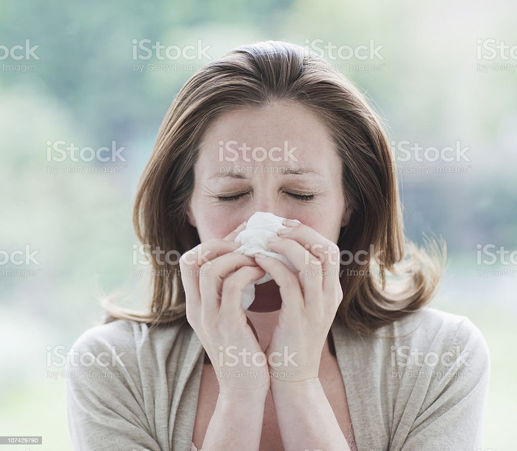 Sick woman wiping her nose stock photo