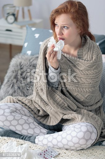 Sick woman with cold, wiping nose with handkerchief while sitting with blanket on bed