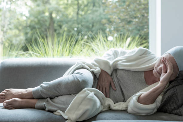Sick woman with a headache lying on a sofa stock photo