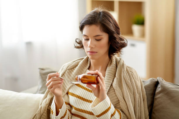 sick woman with antipyretic or cough syrup at home people, health and medicine concept - sad sick young woman in blanket pouring antipyretic or cough syrup from bottle to spoon at home antipyretic stock pictures, royalty-free photos & images