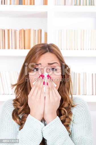 istock sick woman with cold and virus sneezing into tissue 485413075