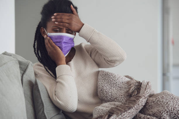 Sick woman with face mask checking temperature. stock photo