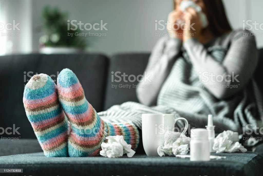 Sick woman with flu, cold, fever and cough sitting on couch at home. Ill person blowing nose and sneezing with tissue and handkerchief. Woolen socks and medicine. Infection in winter. - Foto stock royalty-free di Adulto