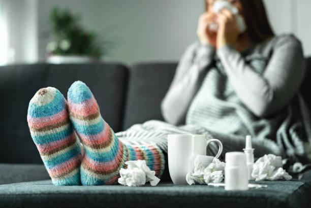 kranke frau mit grippe, kälte, fieber und husten auf couch zu hause sitzen. kranke person nase und niesen mit gewebe und taschentuch. wollsocken und medizin. infektion im winter. - erkältung und grippe stock-fotos und bilder