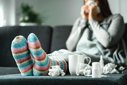 Sick Woman With Flu Cold Fever And Cough Sitting On Couch At Home Ill Person Blowing Nose And Sneezing With Tissue And Handkerchief Woolen Socks And Medicine Infection In Winter - Fotografie stock e altre immagini di Adulto