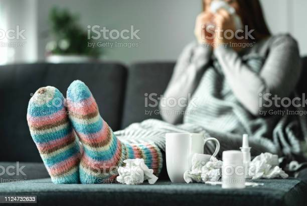 Photo of Sick woman with flu, cold, fever and cough sitting on couch at home. Ill person blowing nose and sneezing with tissue and handkerchief. Woolen socks and medicine. Infection in winter.