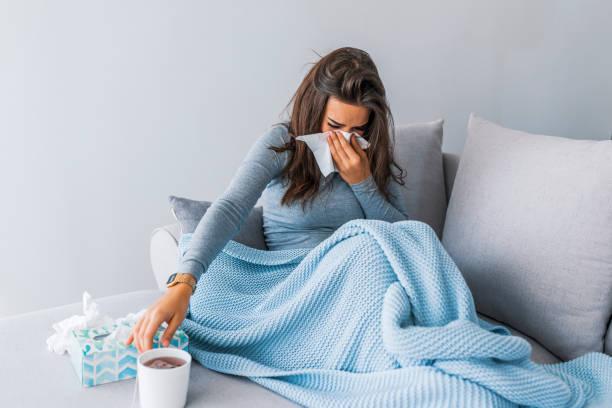 kranke frau mit kopfschmerzen sitzen unter der decke - schnäuzen stock-fotos und bilder
