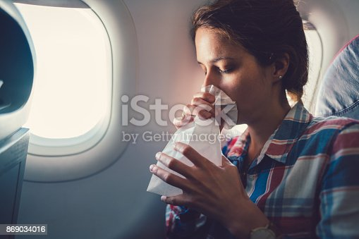 Young woman feeling bad during a flight and breathing in vomit bag