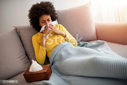 Sick Woman Covered With a Blanket Lying in Bed With High Fever and a Flu, Resting at Living Room. She Is Exhausted and Suffering From Flu. Sick Woman With Runny Nose Lying in Bed