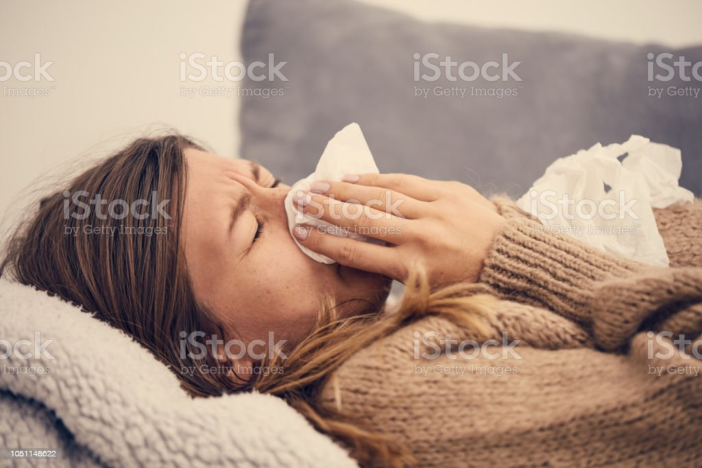 Sick woman with seasonal infections, flu, allergy lying in bed. stock photo