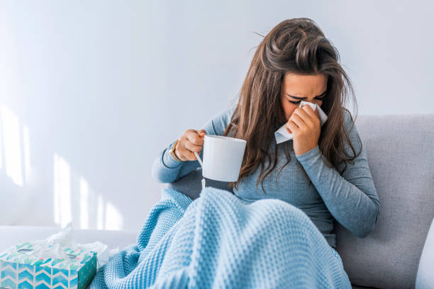 Sick woman with seasonal infections Sick woman with headache sitting under the blanket. Sick woman with seasonal infections, flu, allergy lying in bed. Sick woman covered with a blanket lying in bed with high fever and a flu, resting. flu stock pictures, royalty-free photos & images
