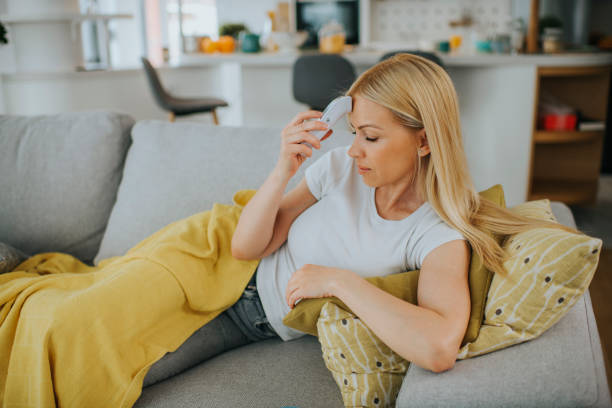 Sick woman with thermometer sitting on bed stock photo stock photo