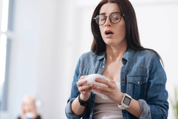 Sick young female while sneezing stock photo