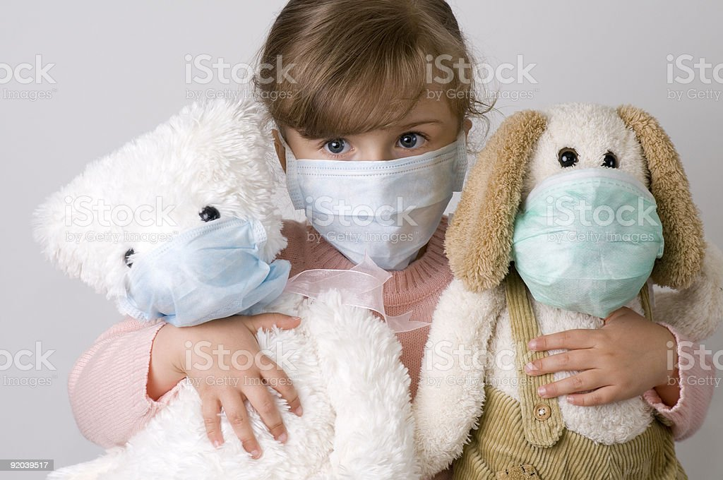 Sick young girl in surgical mask with stuffed animals stock photo