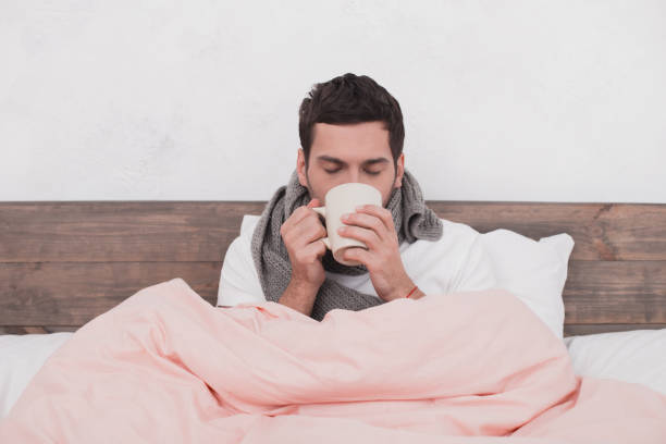 sick young man drinking hot beverage concept - covering stock photos and pictures